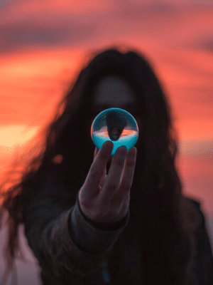Woman with sunrise behind her holding crystal ball reflecting self worth Generative Change