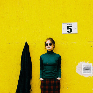 Young woman dressed for job in front of yellow wall waiting generative change