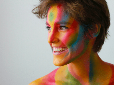 Happy healthy woman smiling colourful paint on face