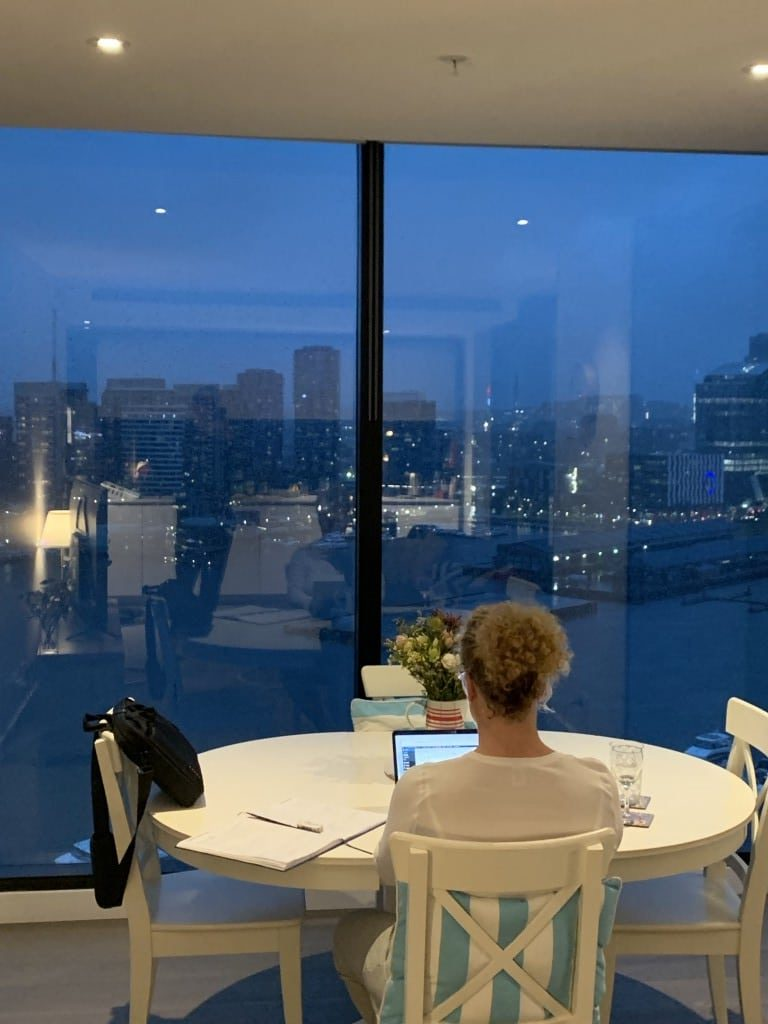 woman sitting at laptop at large window with city view Generative Change Life Changing Coaching Online and By Phone