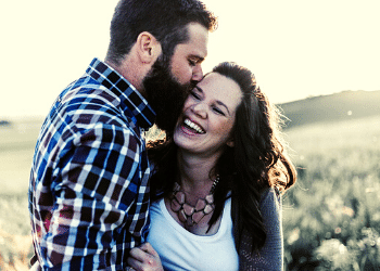 Bearded man kissing a smiling woman in a field Your relationships with others matter Generative Change Life Changing Coaching Online and By Phone