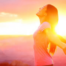 Woman arms outstetched free sunrise