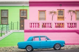 Blue car in front of pink and green buildings covid test for travel Generative Change Life Changing Coaching Online and by phone