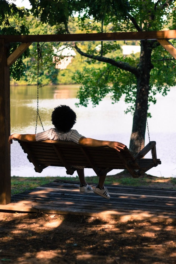 person relaxing on swing seat near lake under trees has turn off notifications Generative Change Life Changing Coaching Online & By Phone